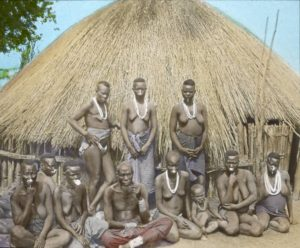 'Man and group of Senga Wives, Livingstonia', unknown photographer, tinted lantern slide, ca. 1910, Church of Scotland Slide and Visual Collection (CSWC47/LS4/19), Centre for the Study of World Christianity, Edinburgh.